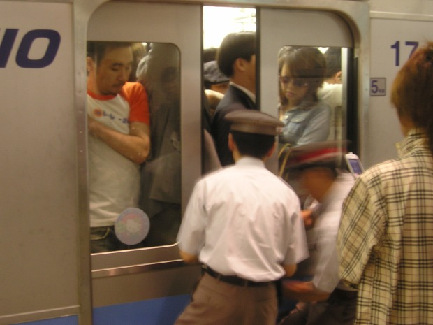 Pushing people onto the Keio line at Shibuya Station
